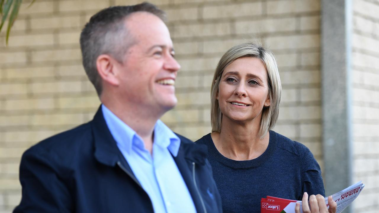 Labor leader Bill Shorten and the party's candidate for the seat of Longman Susan Lamb hand out how-to-vote cards outside a polling booth in Caboolture. Picture: AAP Image/Dan Peled.