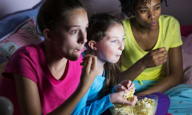 A multi-ethnic group of preteen girls sitting on a bed eating popcorn, watching a movie on television.