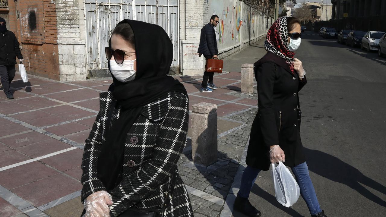 Pedestrians wear face masks and plastic gloves in downtown Tehran, Iran. Picture: AP/Vahid Salemi