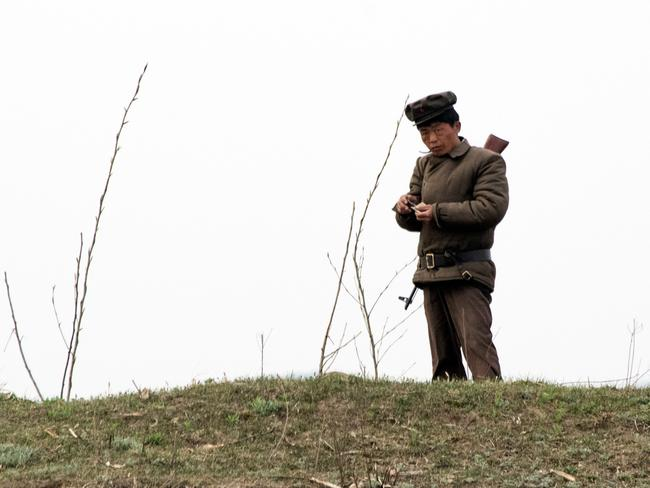 A North Korean soldier rolls a cigarette near the Yalu river near Sinuiju, opposite the Chinese border city of Dandong.