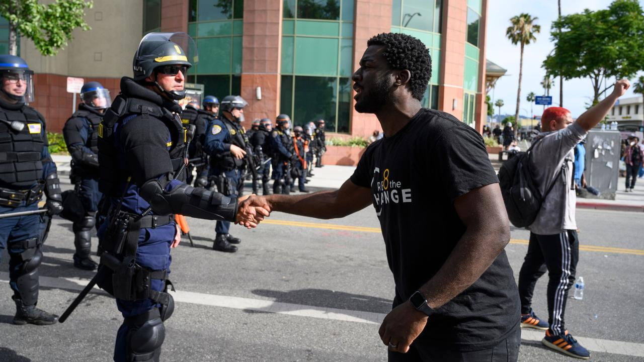 There have been moments of unity such as protester Kevin Welbeck of Cre8 The Change shaking hands with a Highway Patrol officer on June 1 in Los Angeles, California. Picture: Robyn Beck/AFP