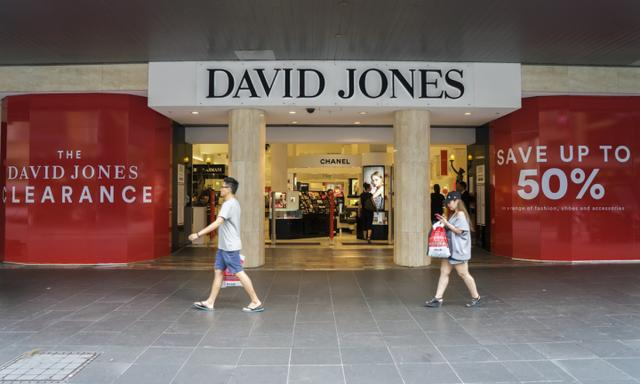 Melbourne, Australia - December 26, 2016: A man and woman walk past the David Jones store at Bourke Street Mall. The department store was open for Boxing Day sales.