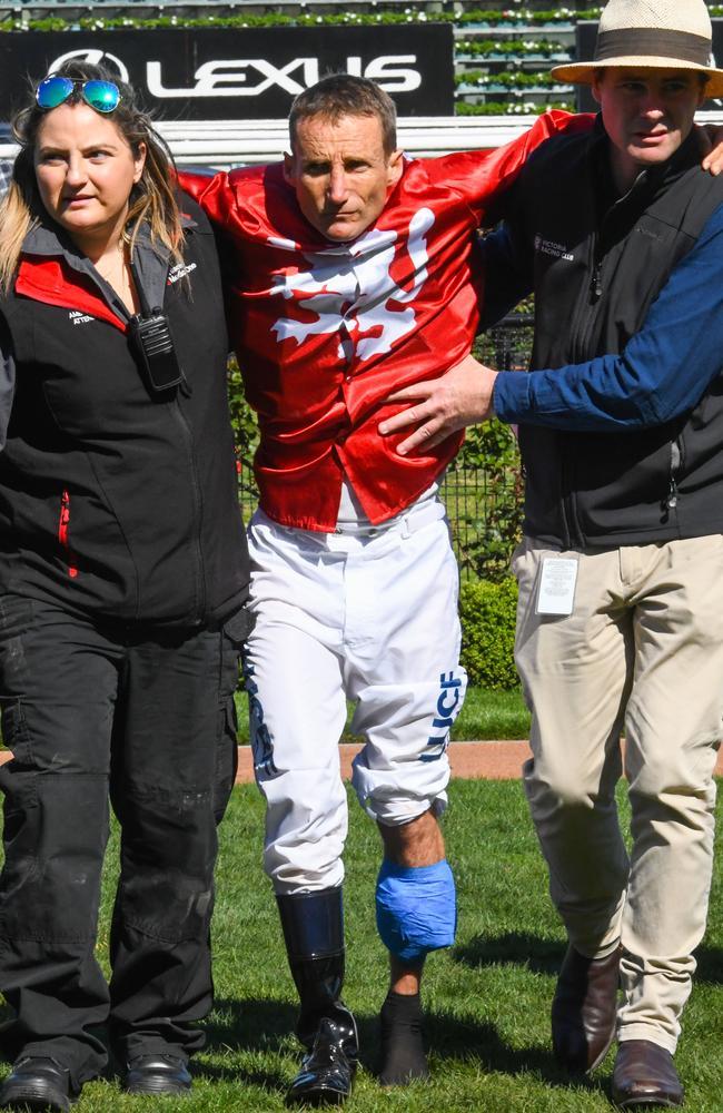 Damien Oliver is helped back into the jockeys' room after the starting gates incident.