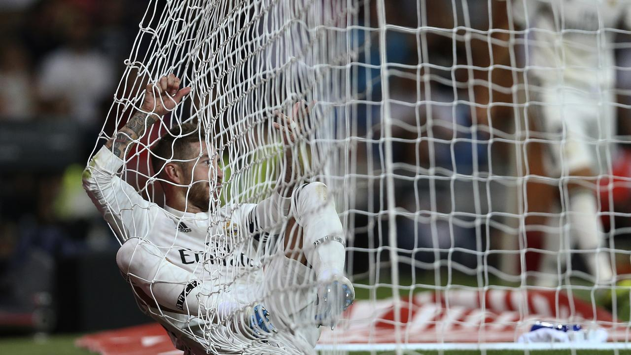 Sergio Ramos lies inside the goal after clearing the ball off the line.