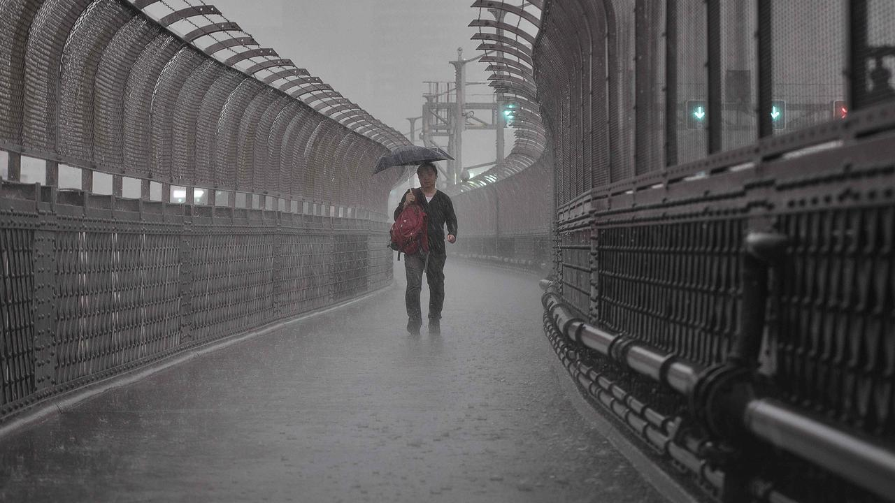 A brolly wasn't going to cut it in drenching rain on the Harbour Bridge. Picture: Flavio Brancaleone