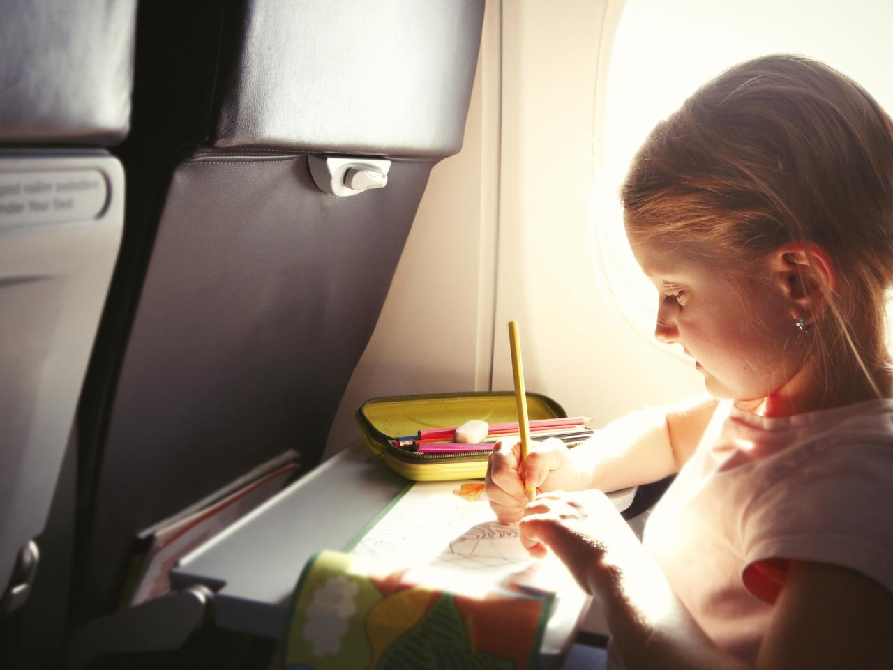 Little girl drawing a picture during flight