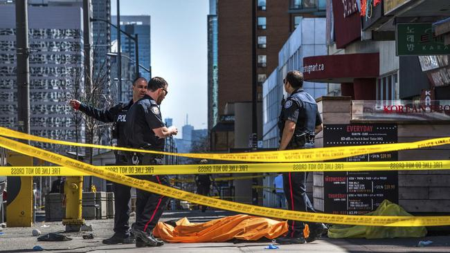 Police officers stand by a body covered on the footpath in Toronto after a van crashed into a crowd of pedestrians. Picture: Aaron Vincent Elkaim/The Canadian Press via AP.