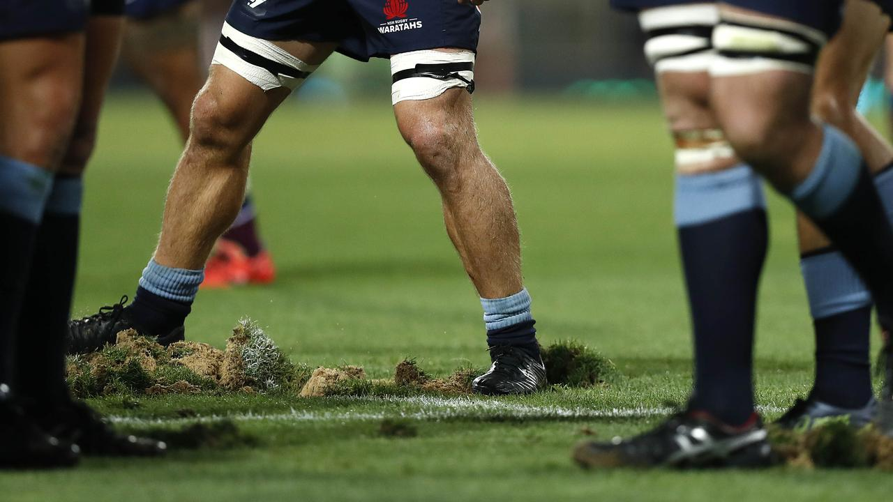 Players replace divots after a scrum at the Sydney Cricket Ground.