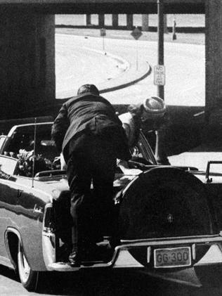 US President John F. Kennedy slumps down in the back seat of the presidential limousine as it speeds along Elm Street toward the Stemmons Freeway overpass in Dallas after being fatally shot. Picture: AP
