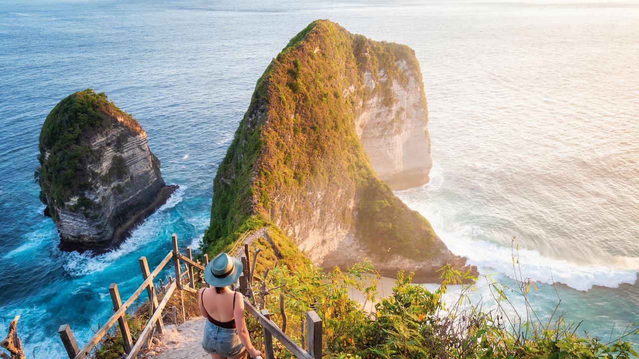 Bali, Indonesia, Traveler Watching the Sunset at Kelingking Beach in Nusa Penida Island