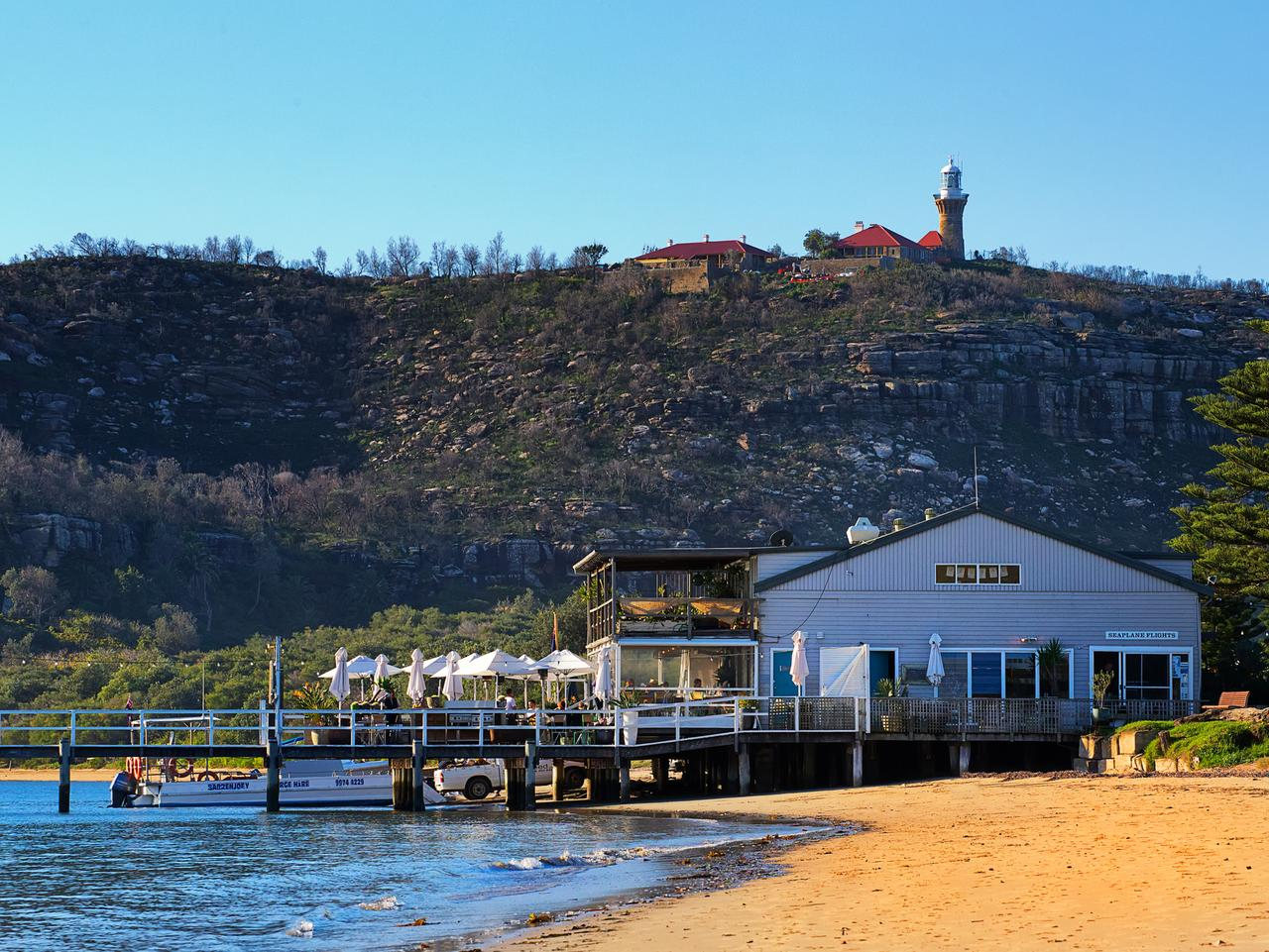 """Palm Beach,Australia - June 11,2014: The Boathouse restaurant with BarrenJoey Head and its lighthouse. The TV drama """"Home and Away"""" is filmed in Palm Beach."""