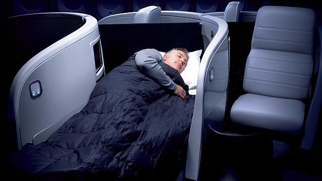 A passenger sleeping in business class on an Air New Zealand flight.