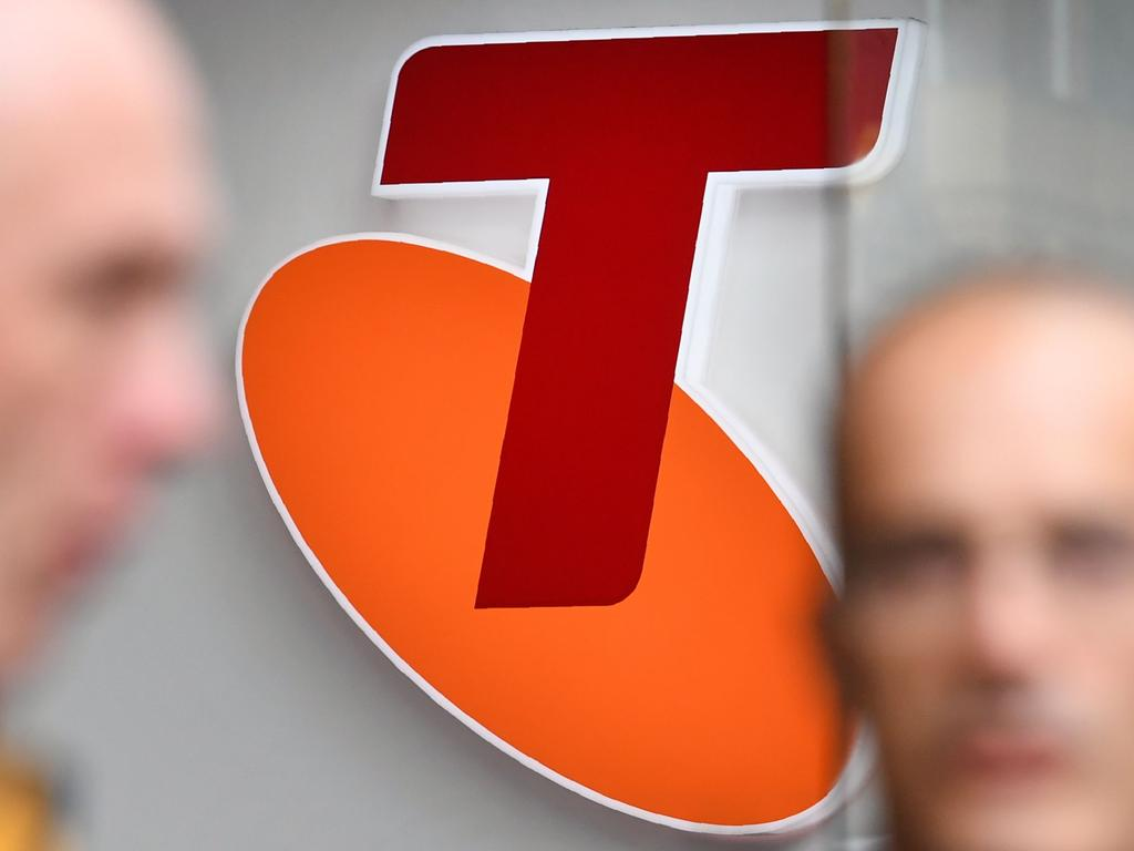 """People walk past a sign of telecommunications company Telstra in Melbourne on August 16, 2018. - Australia's dominant telecommunications company Telstra on August 16 warned of """"enormous challenges"""" ahead as it posted an 8.9 percent slump in annual profit. (Photo by William WEST / AFP)"""