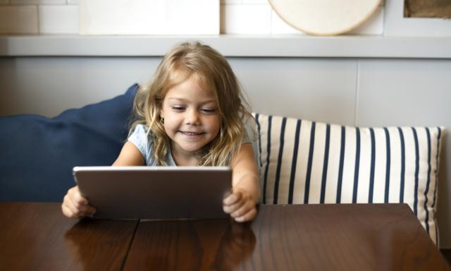 Little girl playing a game on a digital tablet