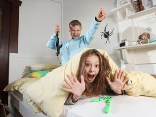 Why pranking could be good for the soul (without going too far). Lifestyle and playful photos of Emily, her husband and their two kids in the yard with pranking props (rubber snakes/spiders). Colourful and casual clothing, eyes to camera shots for SMARTdaily cover photo.    Cassie, 10, and Jake, 8, in their room. Picture: Alex Coppel.