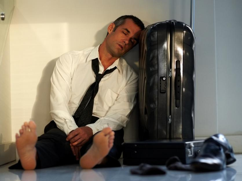 Portrait of a tired businessman sleeping on the floor and waiting due to delay of his flight at airport