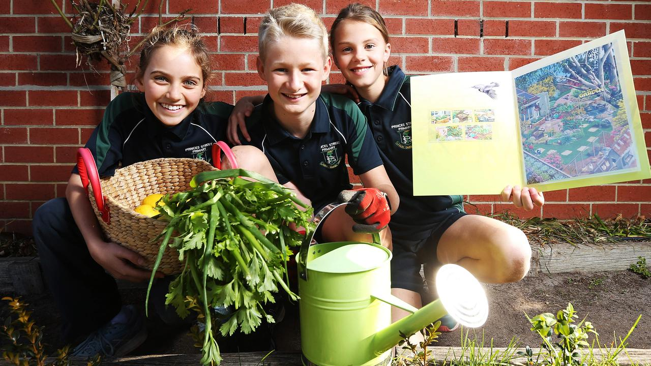 Zara, Tom and Didi from Princes Street Primary School, Tasmania, in their school garden with a set of In the Garden stamps. Picture: Zak Simmonds