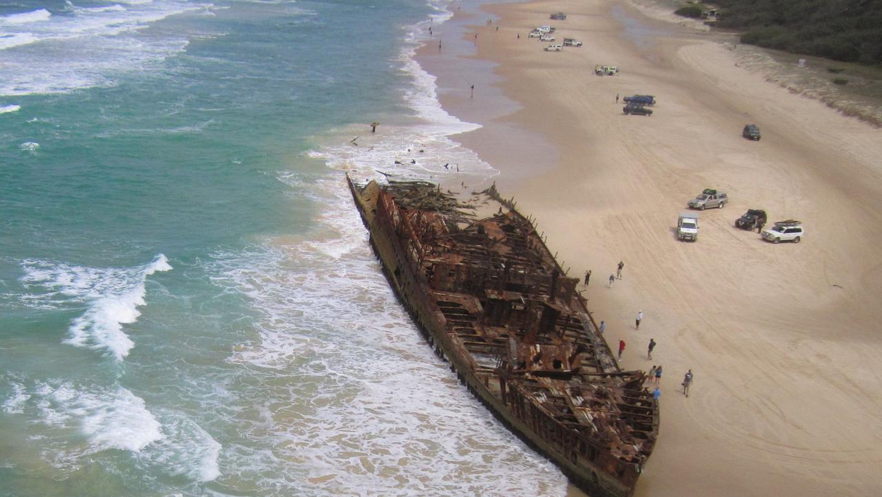 Tourists take their 4WDs on the beach to inspect the Maheno shipwreck.