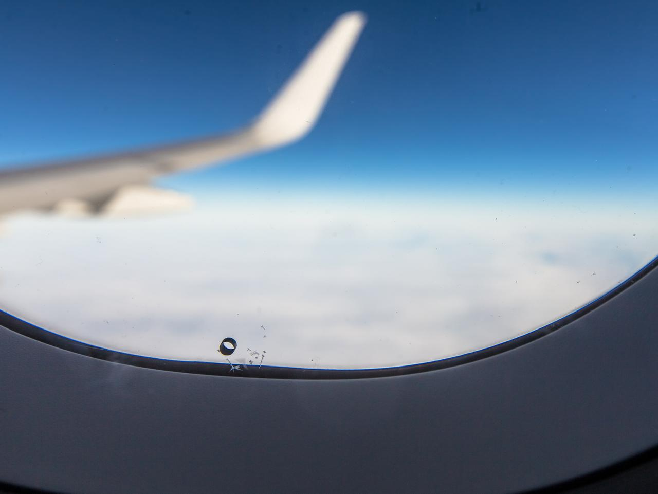 Airplane window breather hole bleed hole with wing blue sky