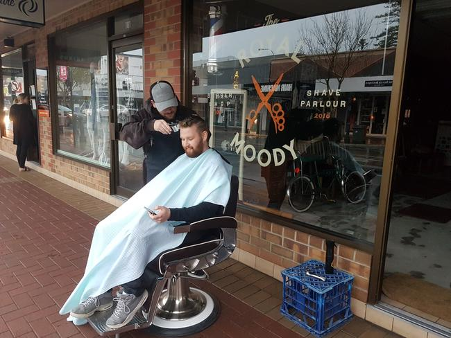 Ben Collins from Blackwood sits outside for his haircut at The Royal Moody after the lights went out across the state. Picture: John Hirst