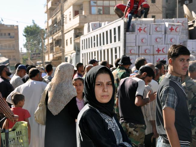 Local residents gather to receive humanitarian aid parcels provided by the Syrian Red Crescent in the northeastern city of Deir Ezzor on September 9, 2017. Picture: AFP