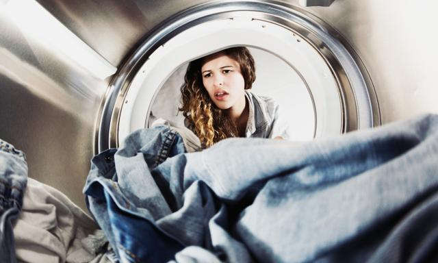 In an unusual view from inside the clothes drier drum, we see a young woman looking unhappy as she reaches in for the laundry; either a job she hates or she has forgotten it and it's still wet!