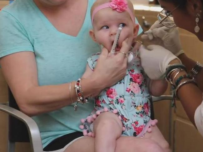 After the markers were placed on the baby's ears, the piercers went to work.