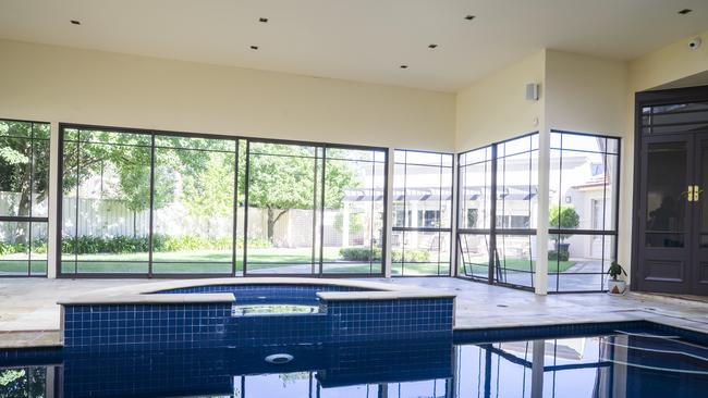 The home includes an indoor swimming pool with large windows overlooking the yard.