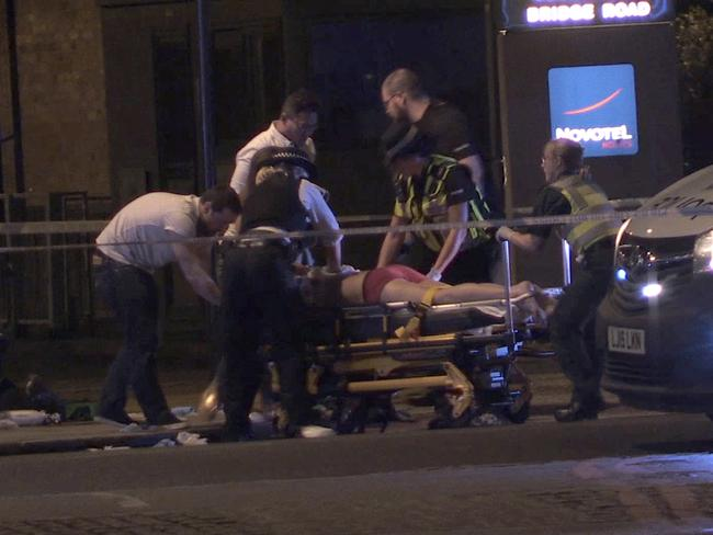 In this image made from PA Video footage, people receive medical attention in Thrale Street near London Bridge. Picture: PA via AP