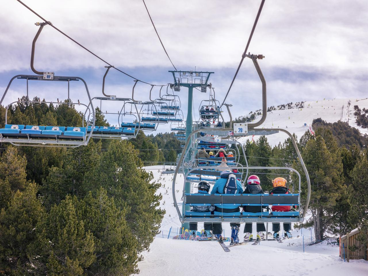 10 February 2019 - El Tarter, Andorra. Picture of skiers using chairlifts in the ski resort of El Tarter. Pinewood forest in the snowy mountains.