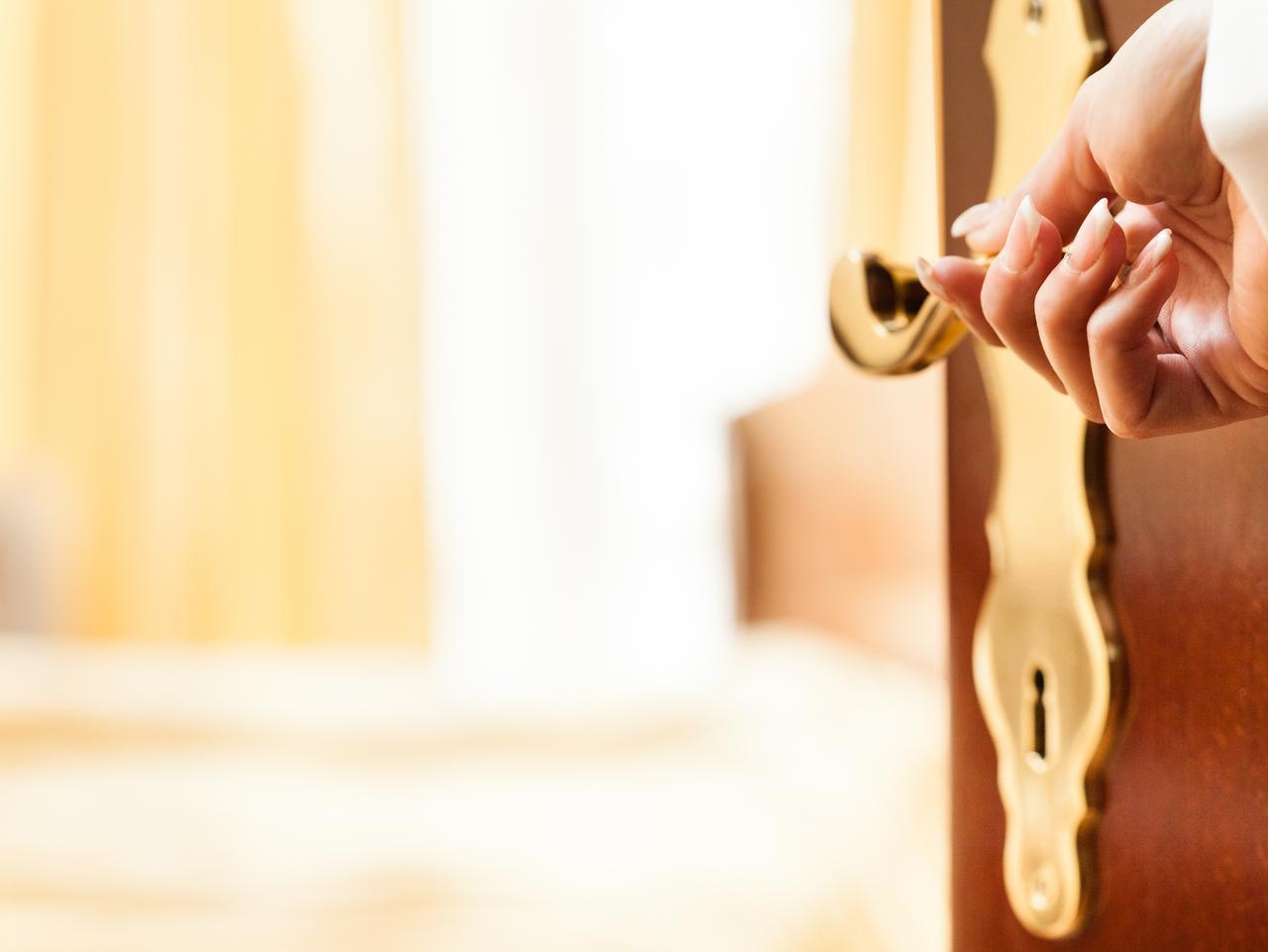 Close-up shot of woman's hand holding door handle, opening door of a hotel room.