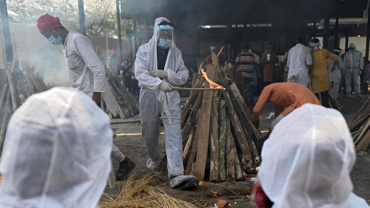 A family member wearing a protective gear performs the last rites of a victim who died of coronavirus at a crematorium in Ghazipur. Picture: Sajjad Hussain/AFP