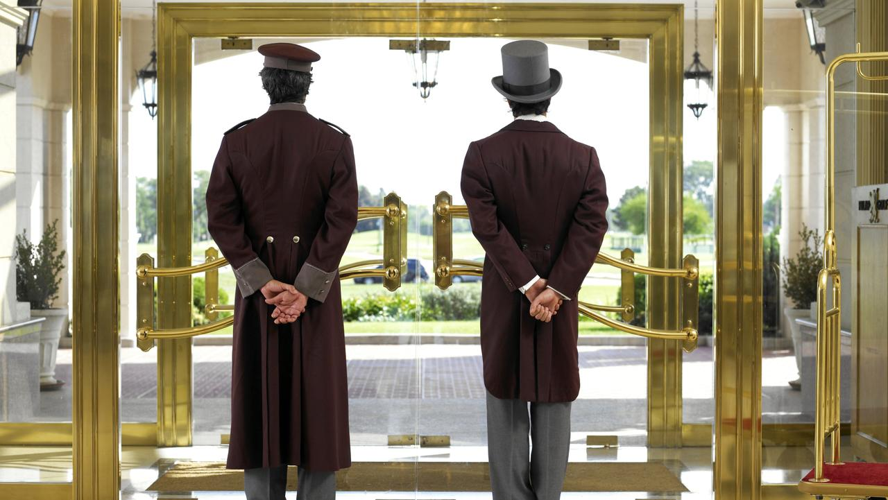 Generic image of a concierge and bellboy standing at a hotel entrance.
