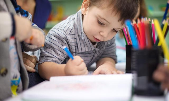 Cute little boy drawing in book with color pencil at preschool classroom. Student using colored pencil at desk in classroom.