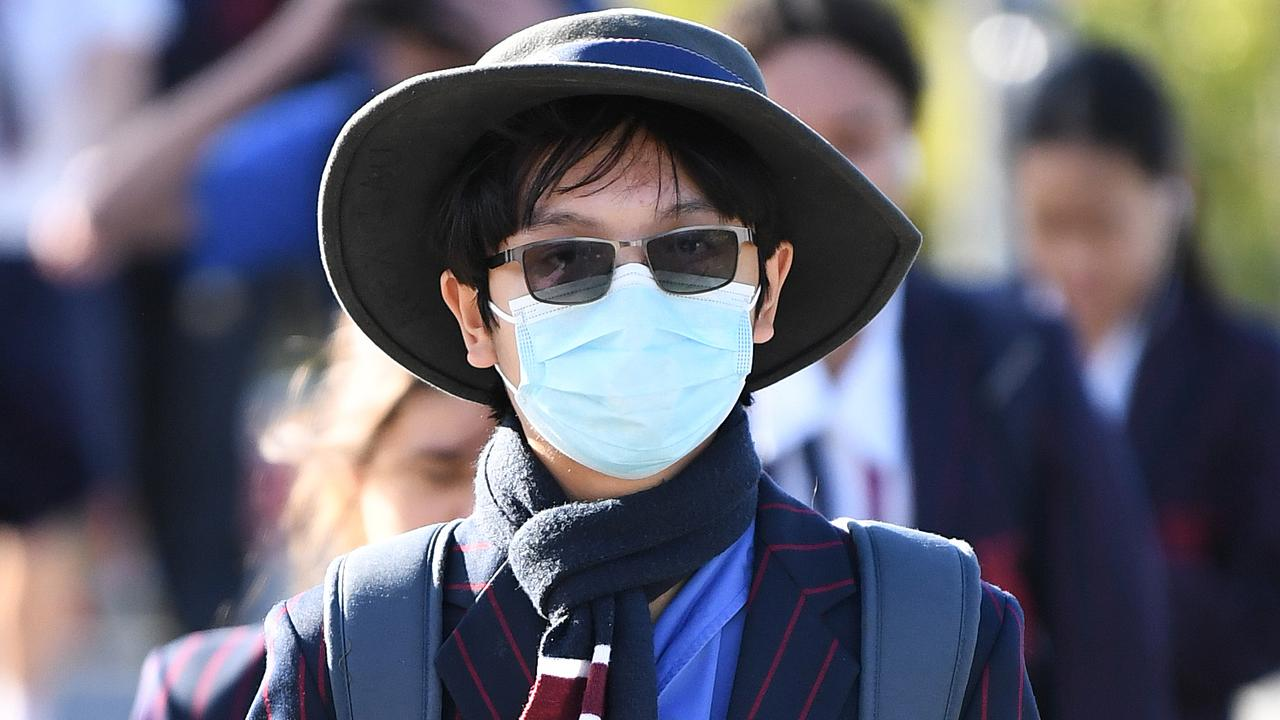 A school student wears a surgical mask as he arrives for the first day of face-to-face schooling in Brisbane today. Picture: Dan Peled/AAP