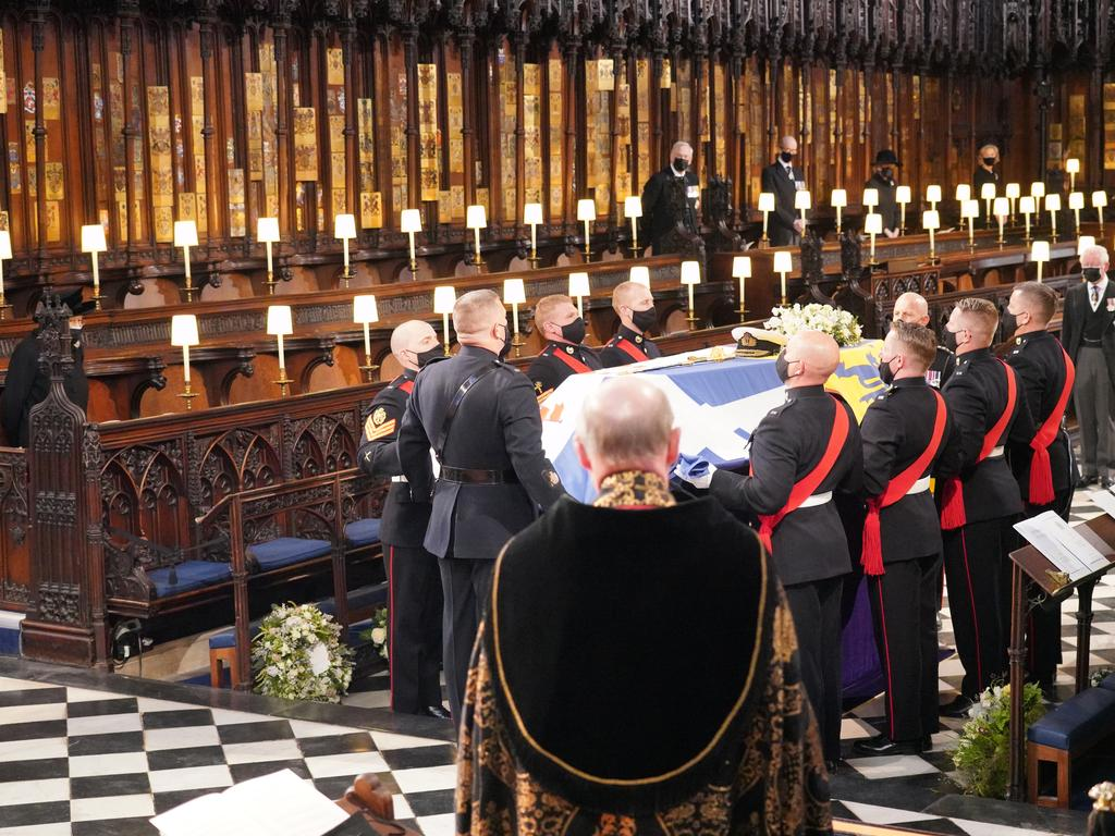 Queen Elizabeth II (left) watches as pall bearers carry the coffin of the Duke of Edinburgh during his funeral in St George's Chapel at Windsor Castle. Picture: WPA Pool/Getty Images