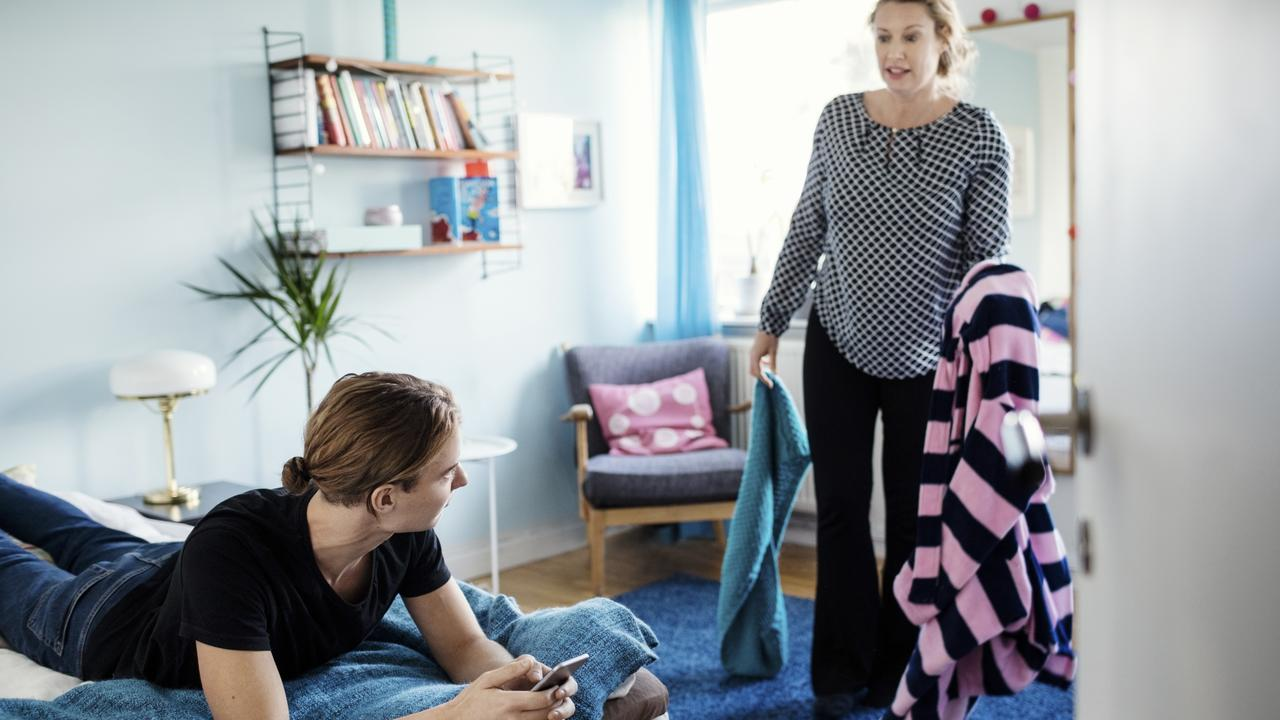 Angry woman holding clothes while looking at son lying on bed at new home