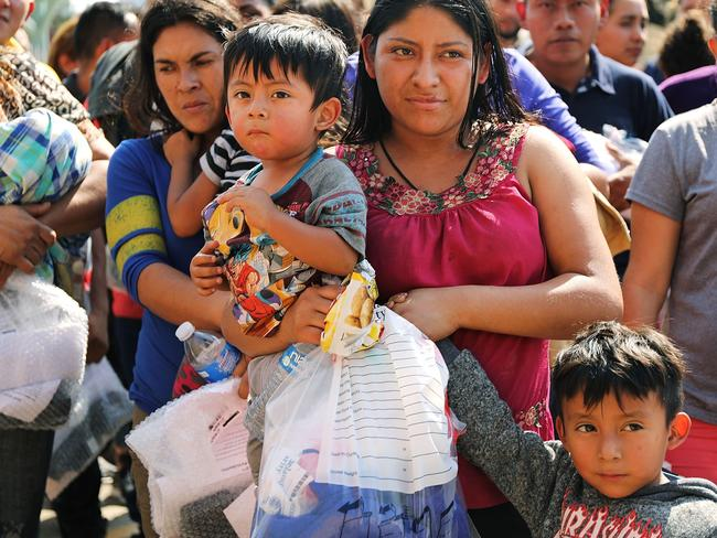 Dozens of women, men and their children, many fleeing poverty and violence in Honduras, Guatamala and El Salvador, arrive at a bus station following release from Customs and Border Protection in McAllen, Texas.