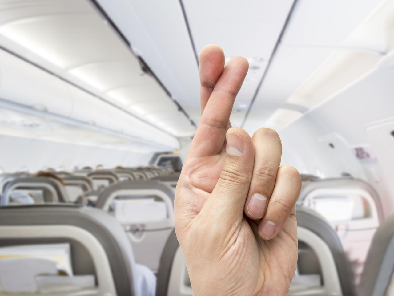 hand crossing the fingers like symbol of superstition to have good luck at the indoor of the plane