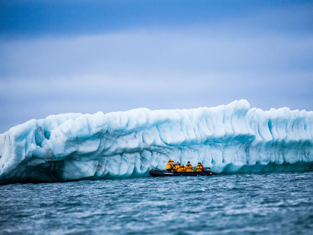 Arctic,Russia - July 29, 2016: Zodiak with tourists in front of Iceberg arctic ocean. Russian Arctic