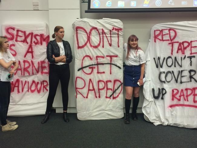 Students stand by the mattresses spray-painted with messages condemning rape. Picture: Nina Dillon Britton
