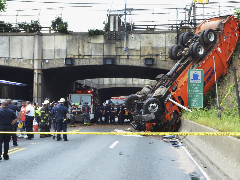 First responders work the scene of a truck accident in Union, City, N.J., not far from the Lincoln Tunnel. The overturned garbage truck blocked a major route out of New York City during the evening commute before the Fourth of July weekend. Picture: AP