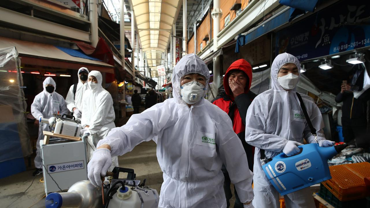 Disinfection professionals in South Korea spray antiseptic solution against the coronavirus. Picture: Chung Sung-Jun/Getty Images