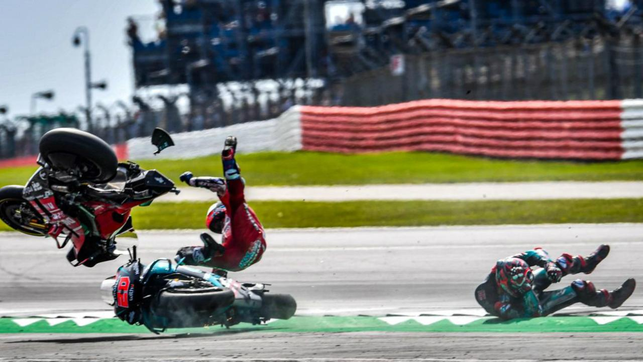 Andrea Dovizioso (L) about to hit the deck following the horror crash. Pic: MotoGP.com