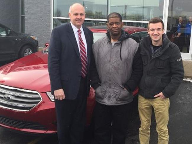 Incredible gift ... James Robertson (centre) in front of his new car with banker Blake Pollock and uni student Evan Leedy at Suburban Ford car dealership in Detroit. Picture: GoFundMe