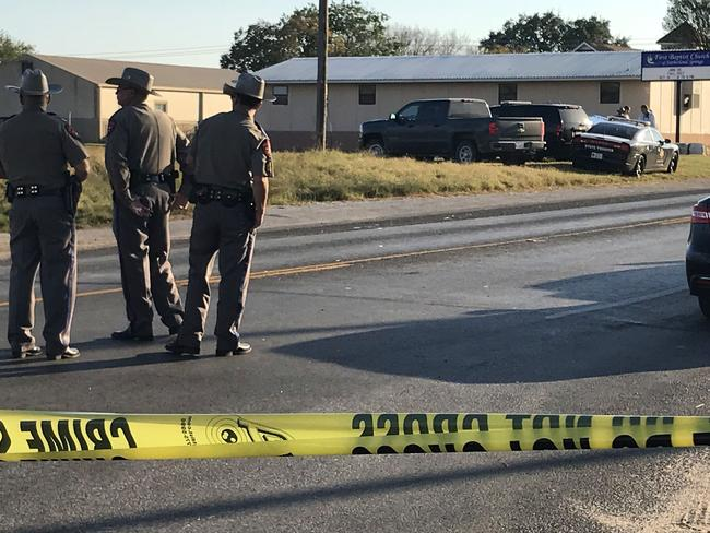 Police block a road in Sutherland Springs, Texas, on November 5, 2017, after a mass shooting at the First Baptist Church (rear). Picture: AFP.