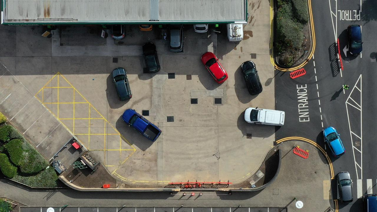 An aerial view shows motorists queuing at a petrol station in Coventry, central England. ease a fuel supply crisis. (Photo by Ben STANSALL / AFP)