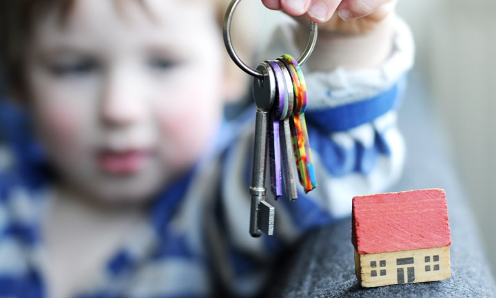 A Three year old boy with toy house and a dummy set of keys. Focus on house, small amount motion blur on keys.