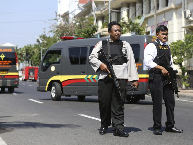 Officers stand guard following an attack at the local police headquarters in Surabaya. Picture: AP
