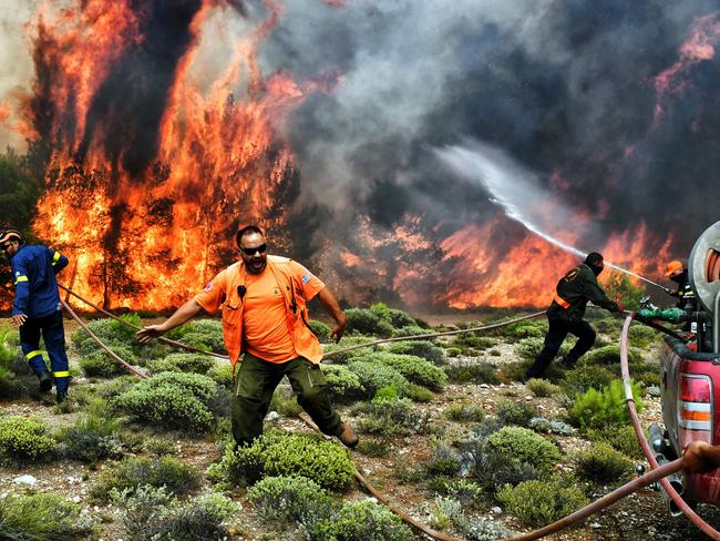 Firefighters and volunteers try to extinguish flames during a wildfire at the village of Kineta, near Athens. Picture: AFP/Valerie Gache